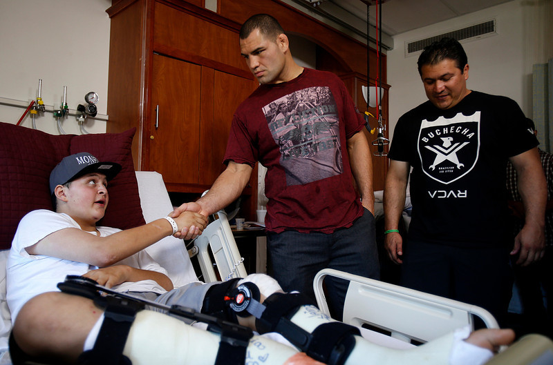 Joseph Supnet-Puerile, left, shakes hands as he says goodbye to UFC heavyweight champion Cain Velasquez during a surprise visit for Heroes Run at Santa Clara Valley Medical Center in San Jose, Calif. on Wednesday, Sept. 18, 2013. Supnet-Puerile was involved in a car accident which killed two of his friends. At far right is Velasquez's coach Javier Mendez. (Nhat V. Meyer/Bay Area News Group)