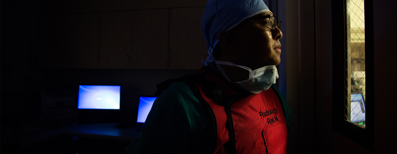 a surgeon in a dark room looking out of the door