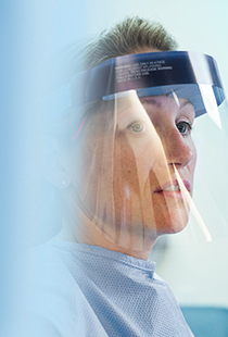 a healthcare worker dressed in scrubs with a protective face visor