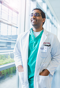 a picture of a healthcare worker smiling and looking out of a window