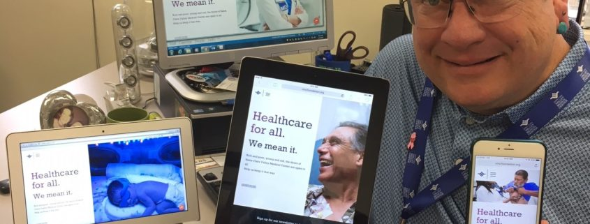 """a picture of Chris Wilder holding up and posing with devices that all say """"Healthcare for all. We mean it."""""""